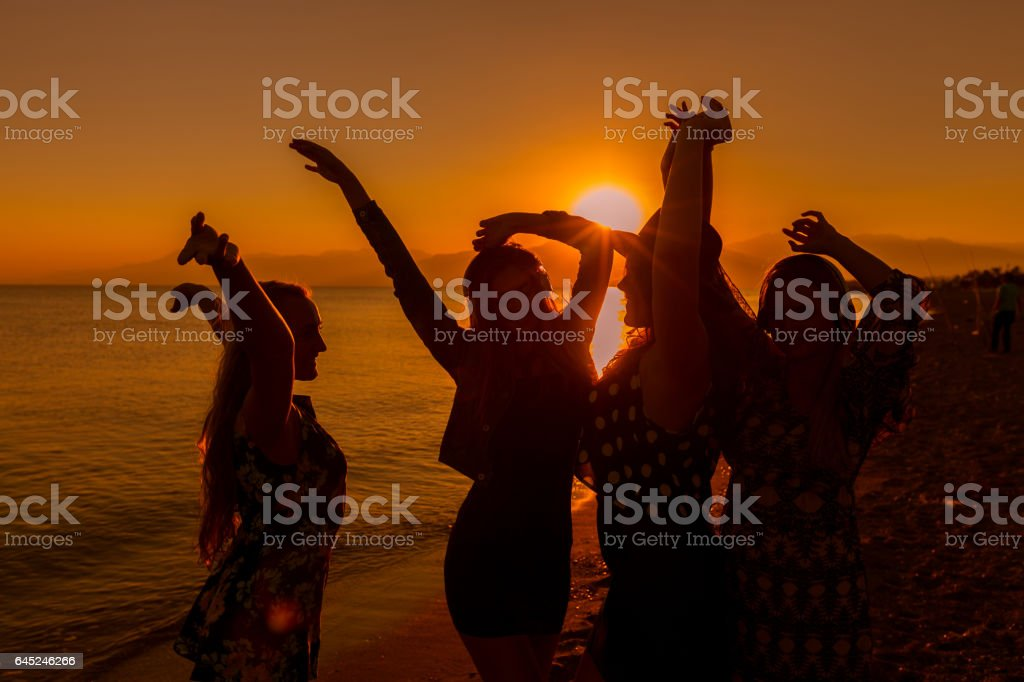 Young friends dancing on the beach at sunset stock photo