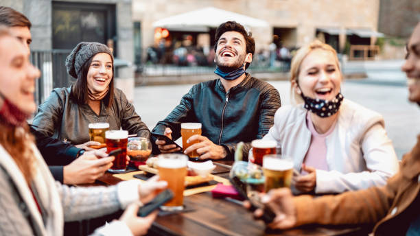 Young friends drinking beer wearing face mask - New normal lifestyle concept with people having fun together talking on happy hour at outside brewery bar - Bright warm filter with focus on central guy stock photo