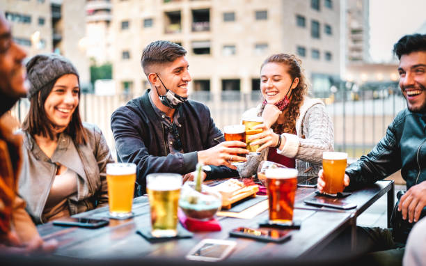 Young friends drinking beer with open face mask - New normal lifestyle concept with milenials having fun together talking at outside brewery bar - Warm filter with focus on left central guy stock photo