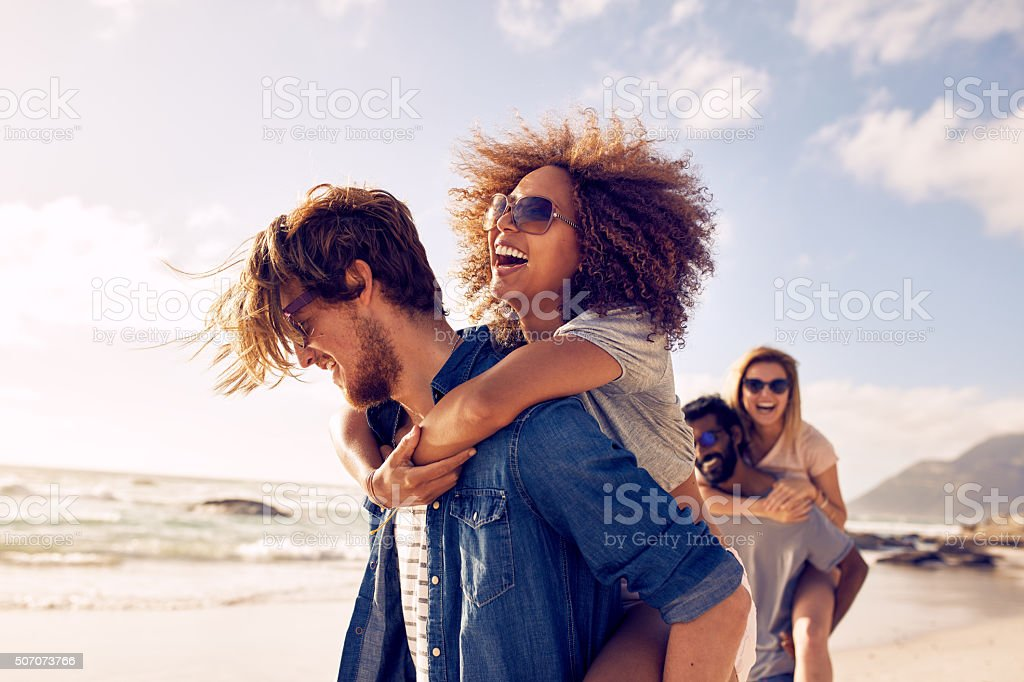 Young friends enjoying a day at beach. stock photo