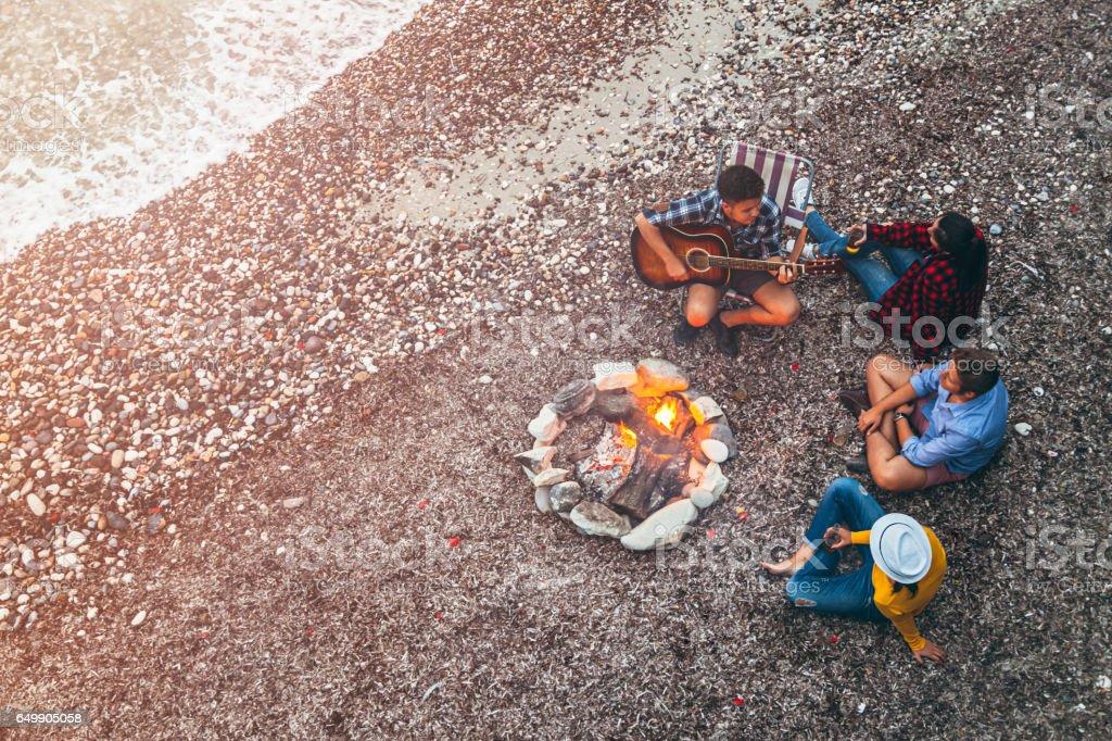 Young friends enjoying music near campfire stock photo