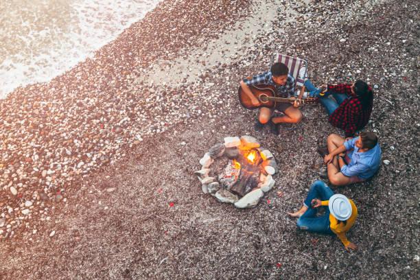 young friends enjoying music near campfire - falò spiaggia foto e immagini stock