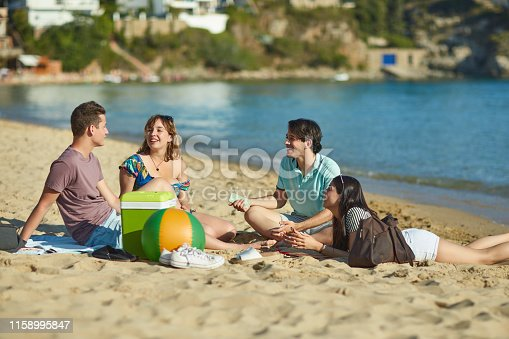Group of young adult friends relaxing and talking on an idyllic Costa Brava beach with lunch in a cooler.