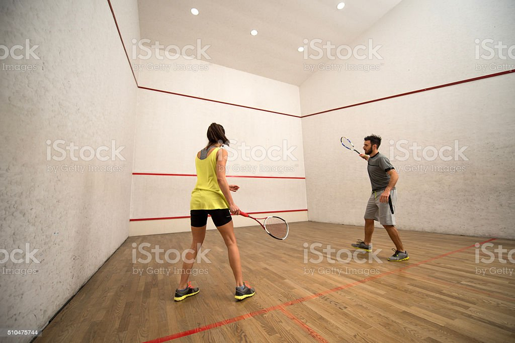 Young friends exercising squash on a court. stock photo