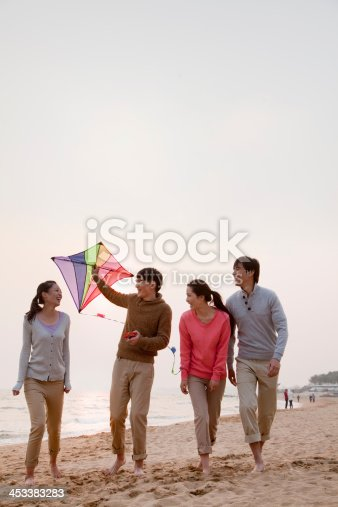 453383283 istock photo Young Friends Flying a Kite on the Beach 453383283