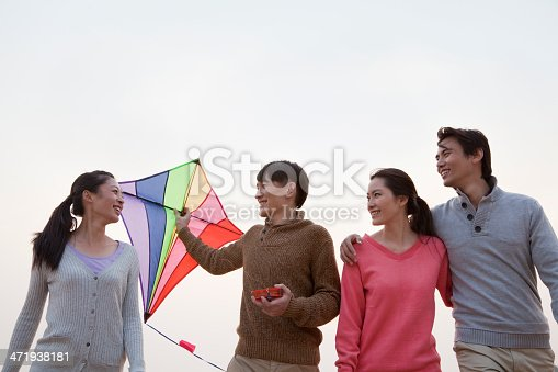 453383283 istock photo Young Friends Flying a Kite on the Beach 471938181