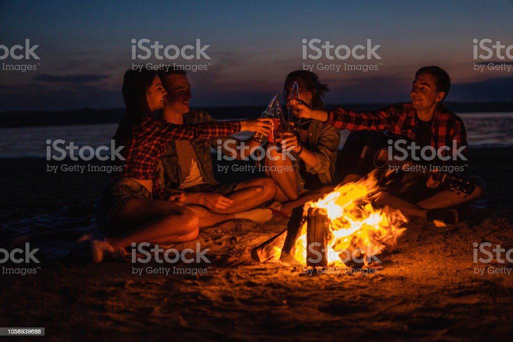 Camp on the beach. Group of young friends having picnic with bonfire...