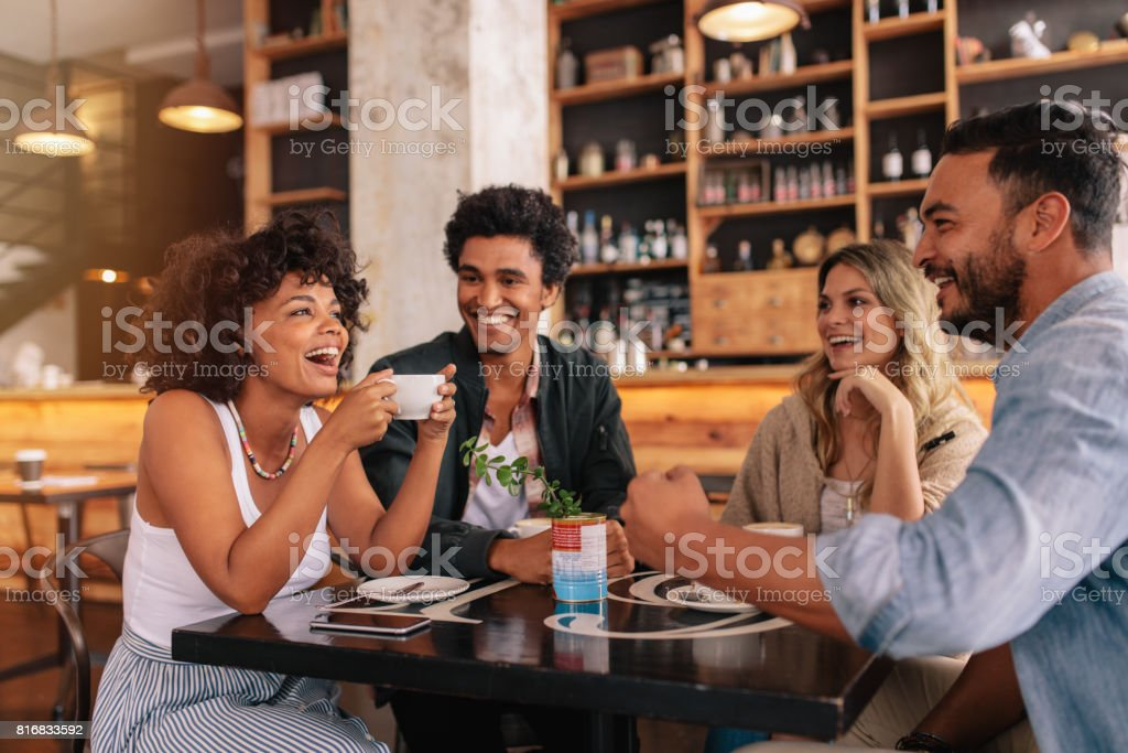 Young friends having a great time in cafe stock photo