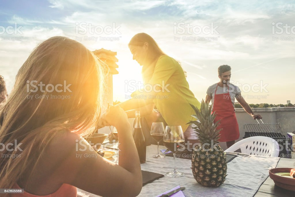 Young friends having barbecue party at sunset on top of the roof - Happy people doing bbq dinner outdoor - Focus on woman smiling - Food, fun and friendship concept - Warm filter stock photo