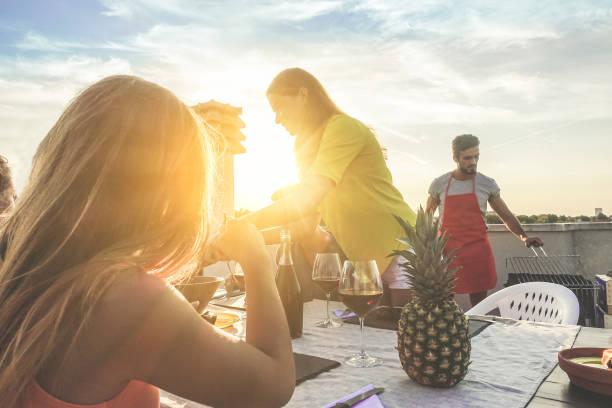 junge freunde grillfest feiern bei sonnenuntergang auf dem dach - glückliche menschen tun grillabend im freien - fokus auf lächelnde frau - essen, spaß und freundschaft konzept - warme filter - tagesgericht stock-fotos und bilder