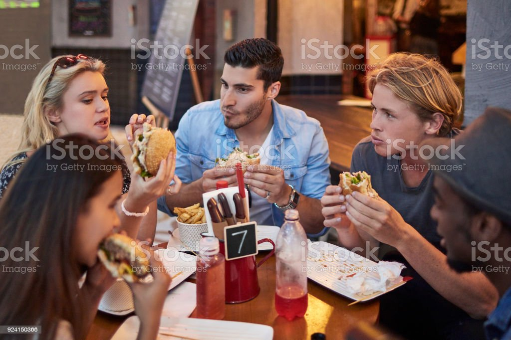 Young friends having burgers in restaurant stock photo