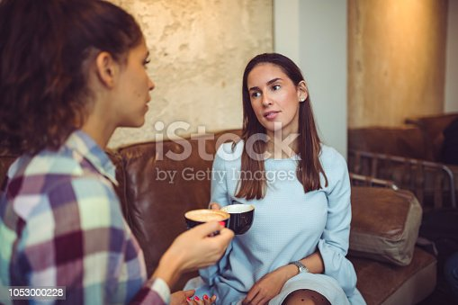 Two young friends having coffee and talking in cafeteria