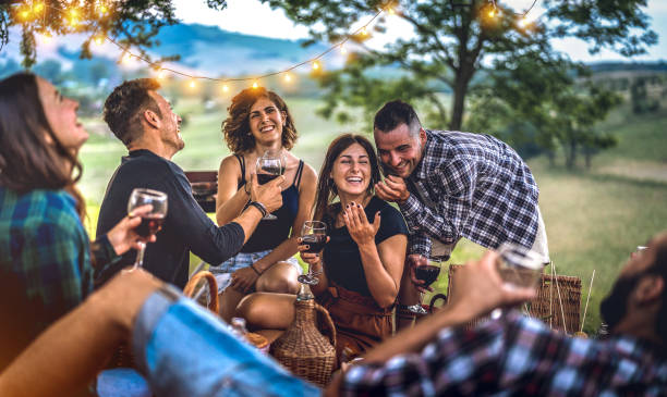 Young friends having fun at vineyard after sunset - Happy people millennial camping at open air pic nic under bulb lights - Youth friendship concept with guys and girls drinking wine at barbeque party stock photo