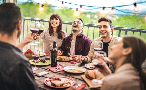 Young friends having fun drinking red wine at balcony penthouse dinner party - Happy people eating bbq food at fancy alternative restaurant together - Dinning lifestyle concept on warm vintage filter stock photo
