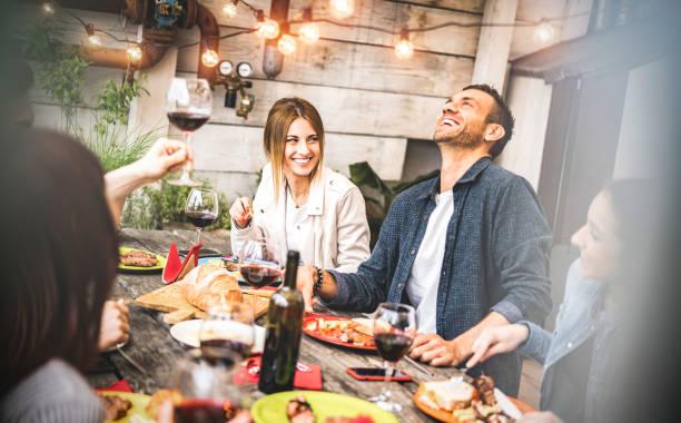 młodzi przyjaciele zabawy picia czerwonego wina na balkonie w domu kolacja - szczęśliwi ludzie jedzący dania z grilla w fantazyjnej restauracji alternatywnej razem - jadalnia koncepcji stylu życia na desaturated filtr - przyjaźń zdjęcia i obrazy z banku zdjęć