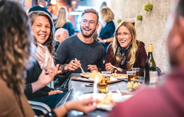 Young friends having fun drinking white wine at street food festival - Happy people eating local plates at open air restaurant together - Travel and dinning lifestyle concept on bulb light neon filter stock photo