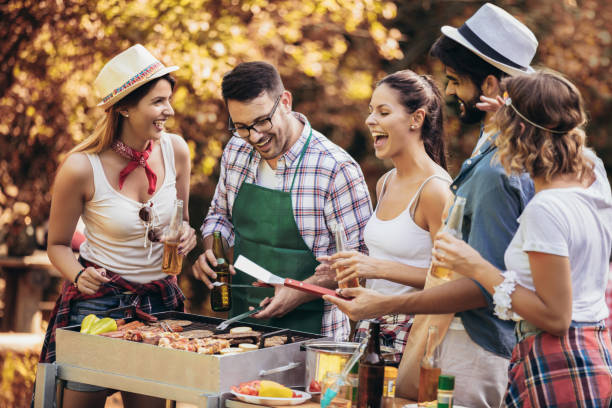 Young friends having fun grilling meat enjoying barbecue party. stock photo