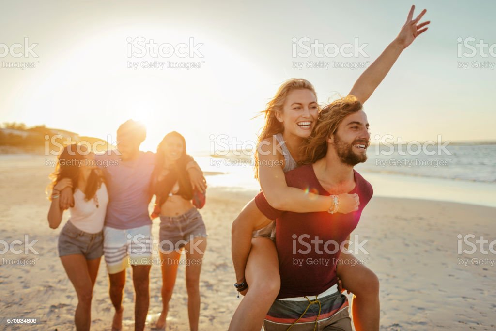 Young friends having fun on the beach stock photo