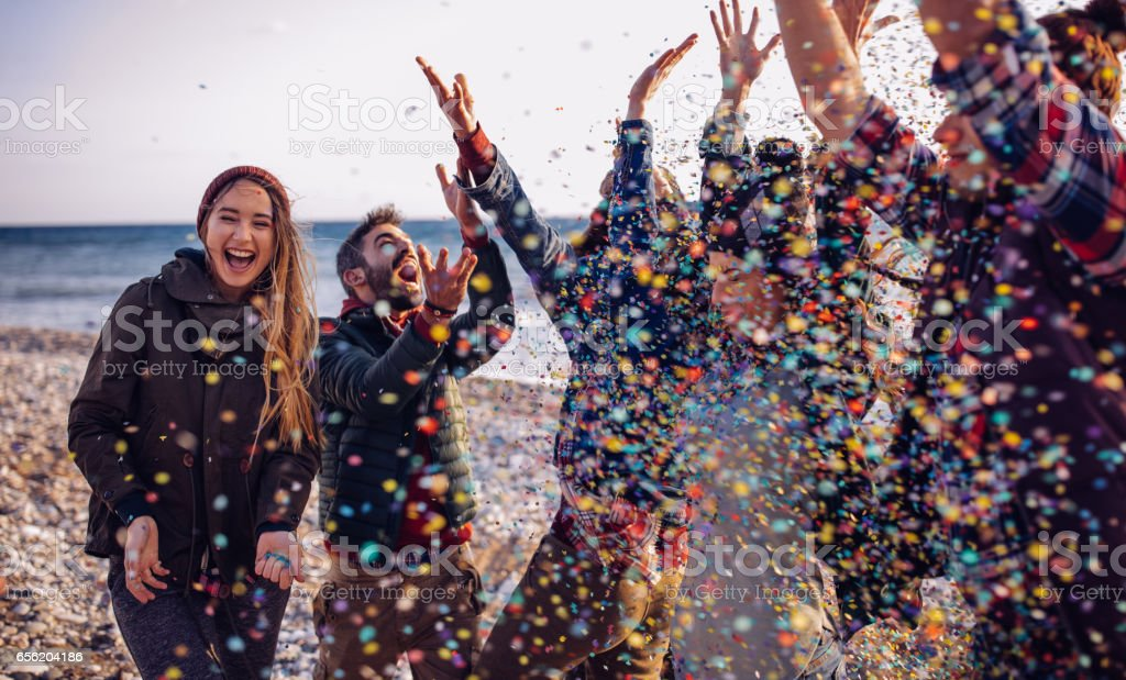 Young friends having fun throwing confetti on a beach stock photo