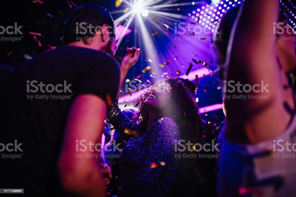 Young friends having fun with confetti on night club party stock photo