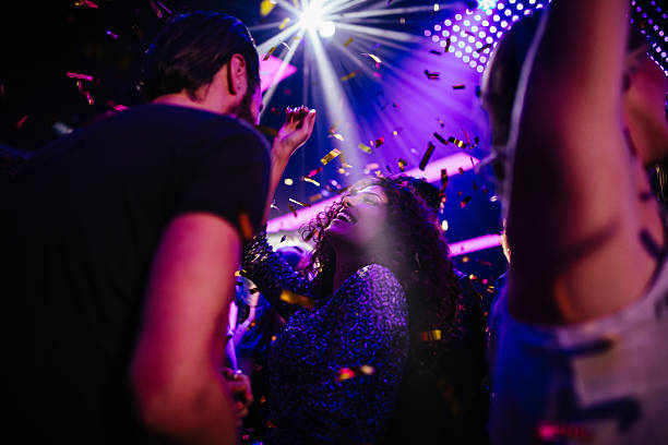 Young friends having fun with confetti on night club party Young adult multi-ethnic group of friends dancing and enjoying a night club party with colorful confetti entertainment club stock pictures, royalty-free photos & images