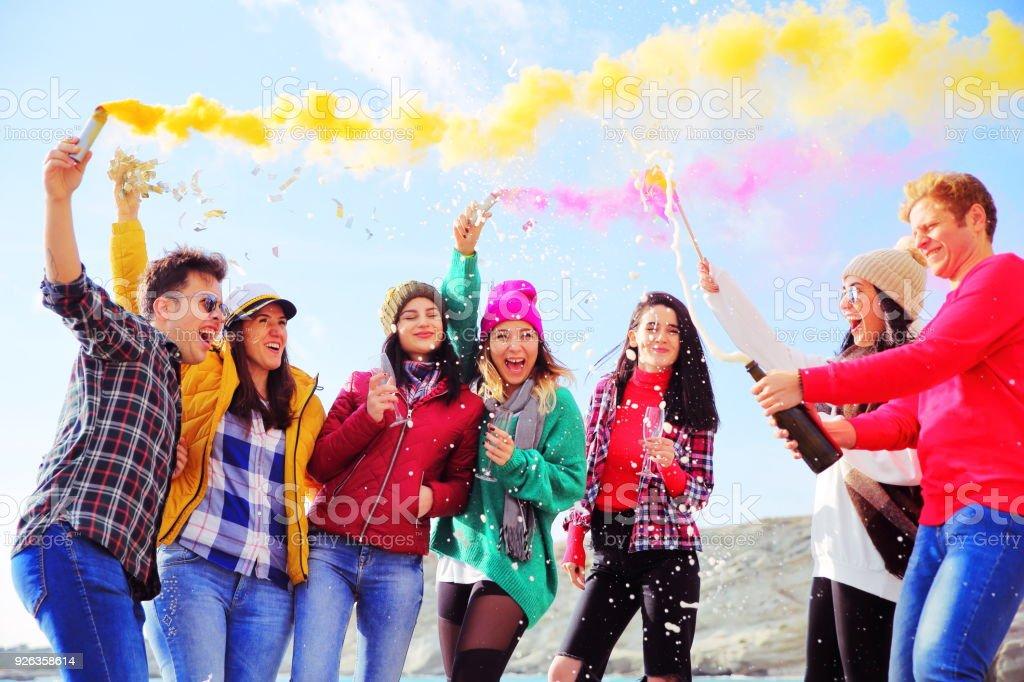 Jóvenes amigos que se divierten con bombas de humo en la playa - foto de stock