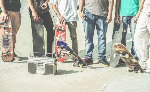 junge freunde skateboards in den händen zu halten, die im freien auf stadt skate park - teen freunde spaß eislaufen und hören musik außerhalb - extremsport, freundschaft, jugendkonzept - retro-kontrastfilter - freundin tattoos stock-fotos und bilder