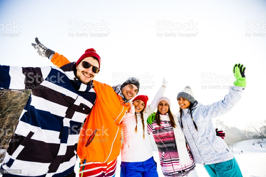 Young friends in ski-wear with arms raised stock photo