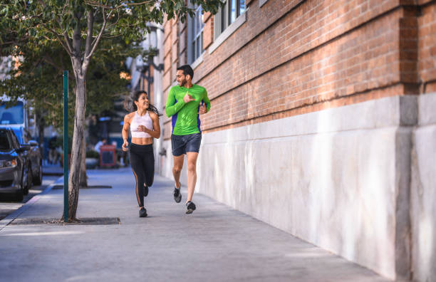 Junge Freunde joggen gemeinsam auf Bürgersteig in Stadt – Foto