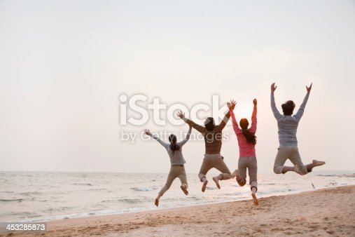 453383283 istock photo Young Friends Jumping at the Beach 453285873
