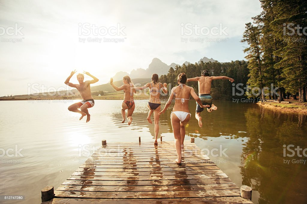Young friends jumping into a lake stock photo