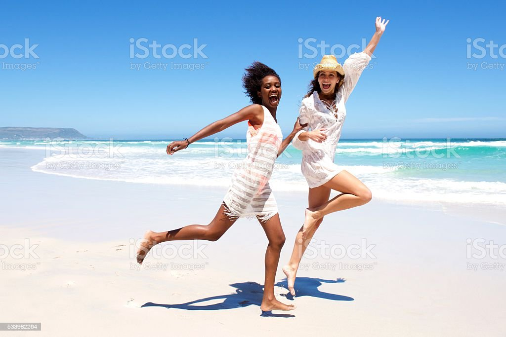 Young friends laughing and running on the beach stock photo