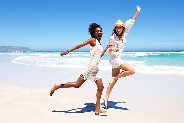 young friends laughing and running on the beach - african youth jumping for joy stock photos and pictures