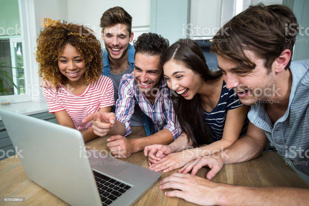 Genç arkadaşlar laptop masaya bakarken gülüyor royalty-free stock photo