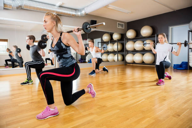 Young Friends Lifting Barbells In Gym stock photo