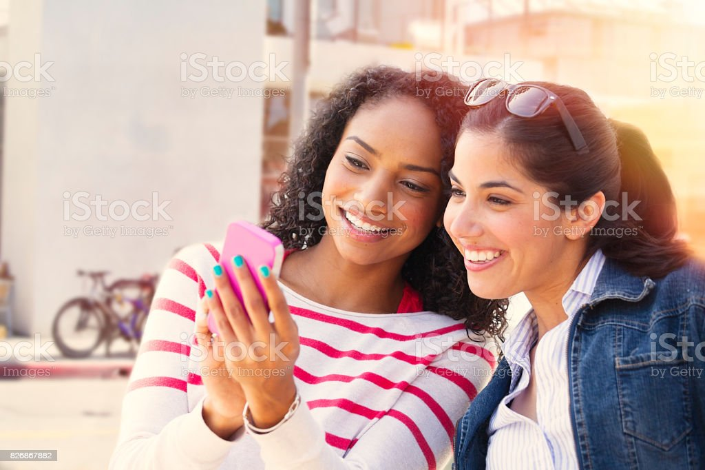 Young friends looking at smart phone stock photo