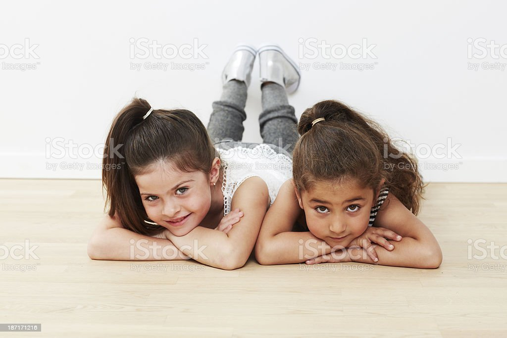 Young friends lying on floor together against white background royalty-free stock photo