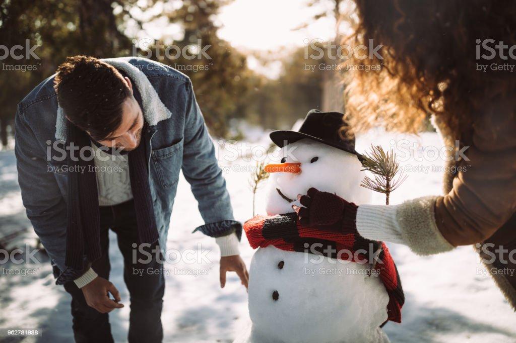 Jovens amigos, fazendo boneco de neve na neve no inverno - Foto de stock de 20 Anos royalty-free