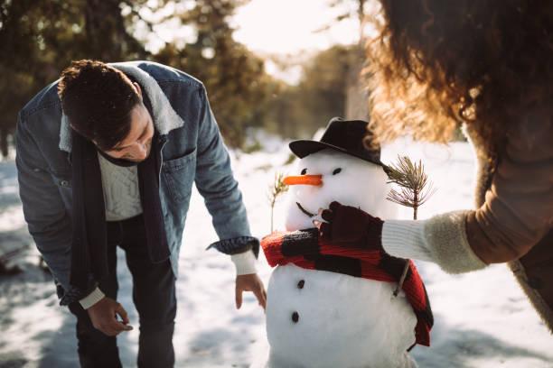 junge freunde machen schneemann im schnee im winter - schneemann bauen stock-fotos und bilder