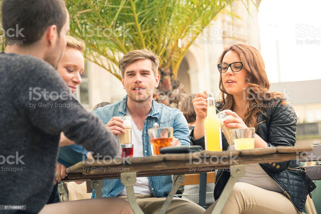 Young friends meeting and drinking in sidewalk cafe. stock photo