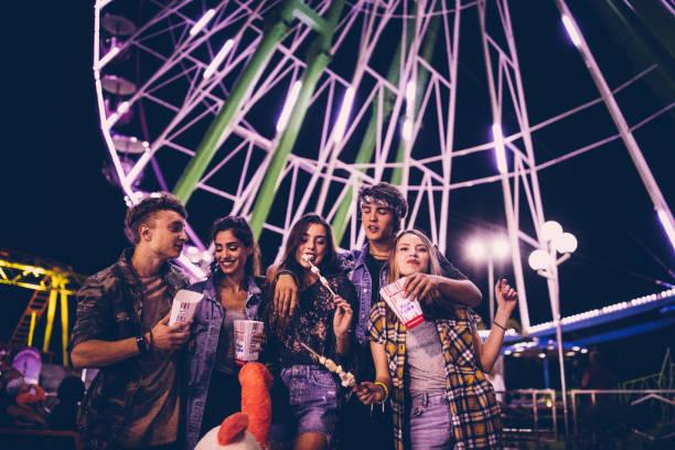 junge freunde ausgehen im freizeitpark - mädchen night snacks stock-fotos und bilder