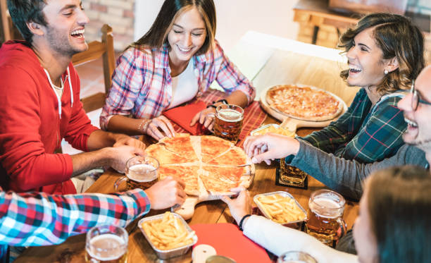 Young friends on genuine laugh while eating pizza at home on family reunion - Friendship concept with happy people enjoying time together having fun at pizzeria drinking brew pints - Warm vivid filter stock photo