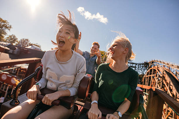 young friends on thrilling roller coaster ride - attractiepark stockfoto's en -beelden
