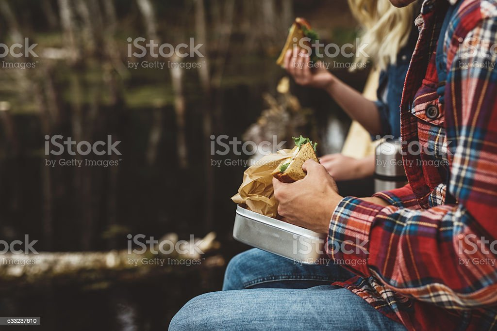 Young friends out on a hike eating food stock photo