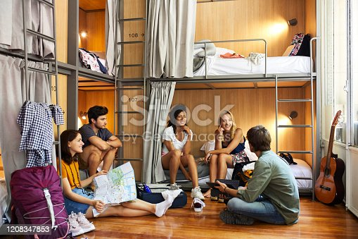 Young friends planning trip by bunkbeds. Male and female backpackers are discussing in dorm room. They are enjoying at hostel.