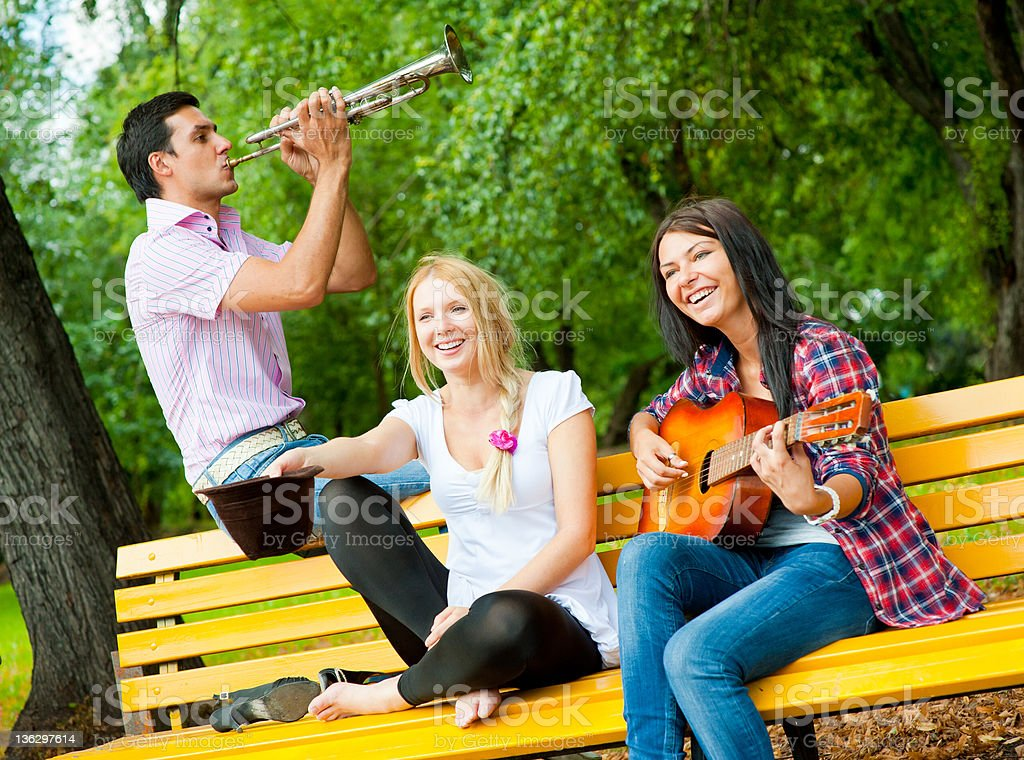 Young friends play the guitar and trumpet royalty-free stock photo