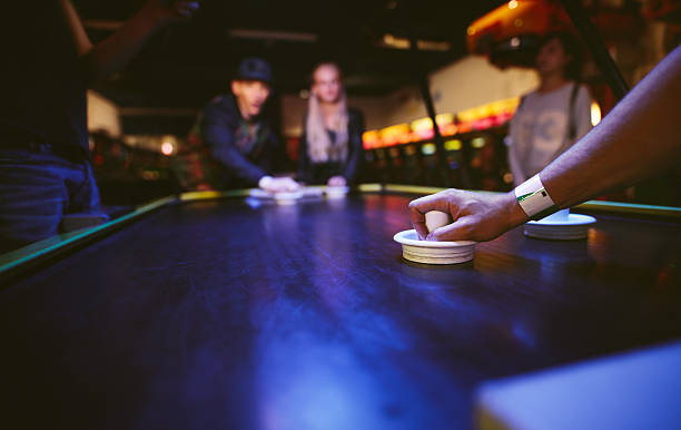 Young friends playing air hockey game - foto de acervo