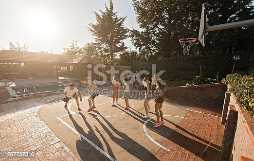 Group of young friends, men and women on a basketball field playing basketball