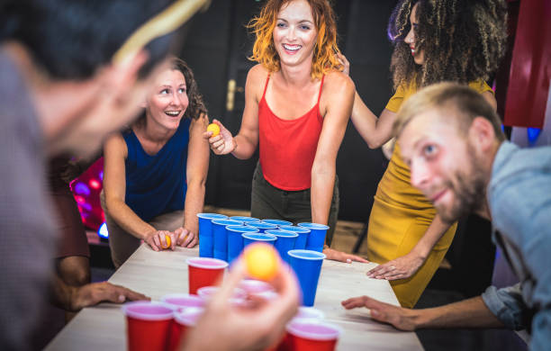 young friends playing beer pong at youth hostel - free time travel concept with backpackers having unplugged fun at guesthouse - happy people on playful genuine attitude - vivid vignetting filter - beirut foto e immagini stock