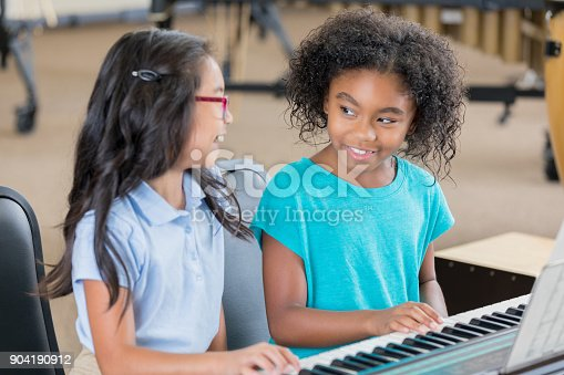 Happy schoolgirls enjoy playing the keyboard together during music class. They are smiling and laughing as they play the keyboard.